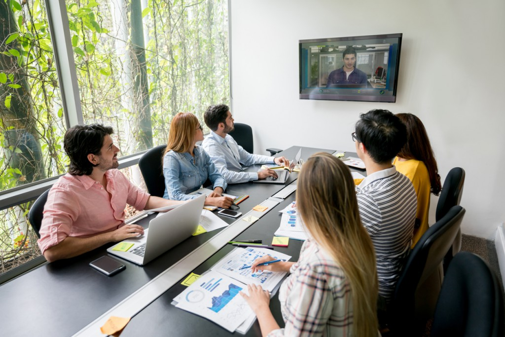 Group of people in a meeting at a creative office making a video conference